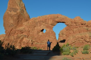 A peek around her son at Arches.